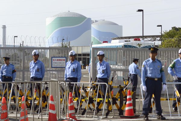 Police officers and security guards stand in front of the main gate to the the Sendai Nuclear Power Station as No. 1 reactor, left, and No. 2 reactor stand in Satsumasendai, Japan, on Tuesday.