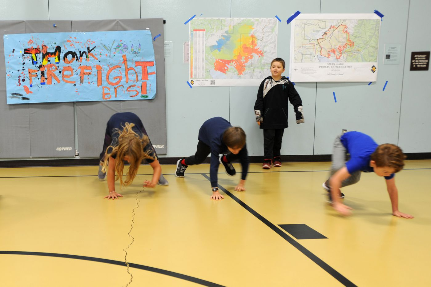 Students at the Cooper Landing school exercise in the gym Sept. 6, 2019. The school has been used for community meetings so collections of maps, as well as thank-you signs, adorn the walls. (Anne Raup / ADN)