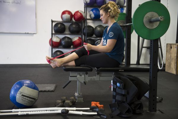 Rosie Mancari does physical therapy exercises during a workout at CrossFit Alaska in South Anchorage. Mancari, a Team USA snowboardcross racer, is recovering in Anchorage after she ruptured two Achilles tendons on a training day at the Winter Olympics in Pyeongchang, South Korea, in February. Photographed on March 13, 2018. (Marc Lester / ADN)