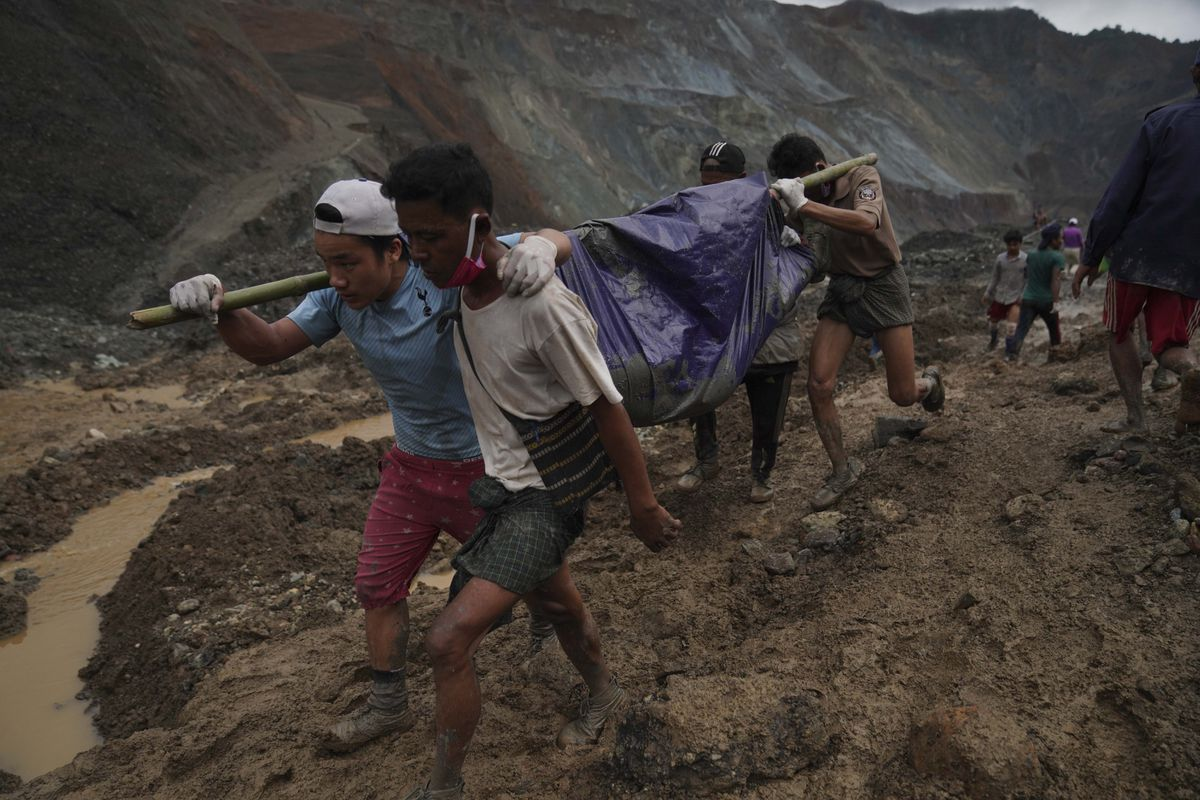 Rescue workers use poles to carry a body shrouded in blue and red plastic sheet Thursday, July 2, 2020, in Hpakant, Kachin State, Myanmar. At least 162 people were killed Thursday in a landslide at a jade mine in northern Myanmar, the worst in a series of deadly accidents at such sites in recent years that critics blame on the government's failure to take action against unsafe conditions. (AP Photo / Zaw Moe Htet)