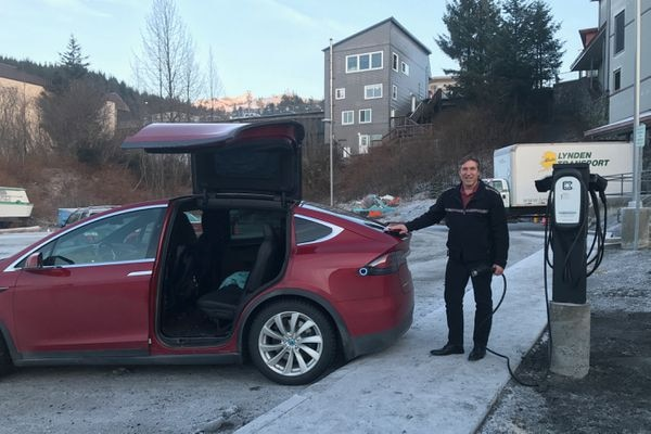 Cordova mayor Clay Koplin demonstrates charging an electric car with a recently installed electric vehicle charging station. January 2018. (Photo by John Harvill)