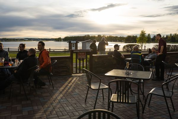 People take in the sunset from the deck at the Fancy Moose Lounge on the Lake Hood Seaplane Base Friday, May 25, 2018. (Loren Holmes / ADN)