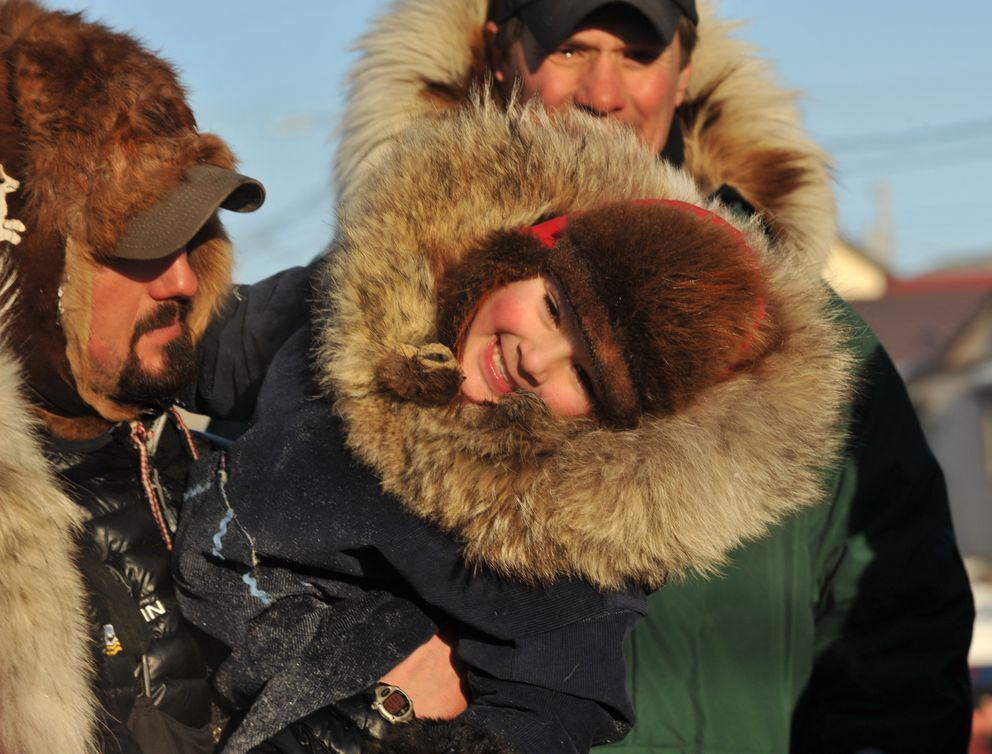 Iditarod musher Pete Kaiser holds his son Ari Kaiser as they pose for photos after Pete finished the 2017 Iditarod Trail Sled Dog Race on Wednesday. (Bob Hallinen / Alaska Dispatch News)