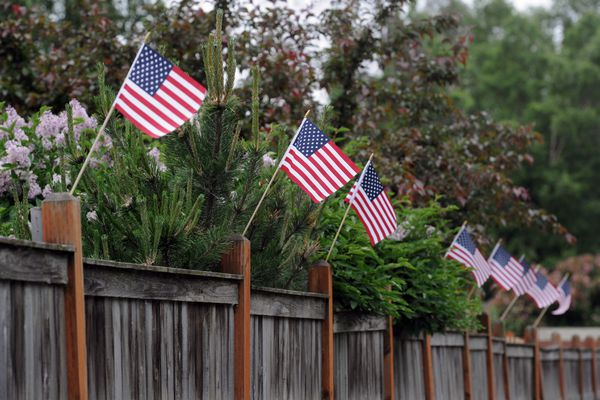 Flags for the 4th line a fence along West Northern Lights Boulevard on Monday, July 3, 2017, in west Anchorage. (Erik Hill / Alaska Dispatch News)