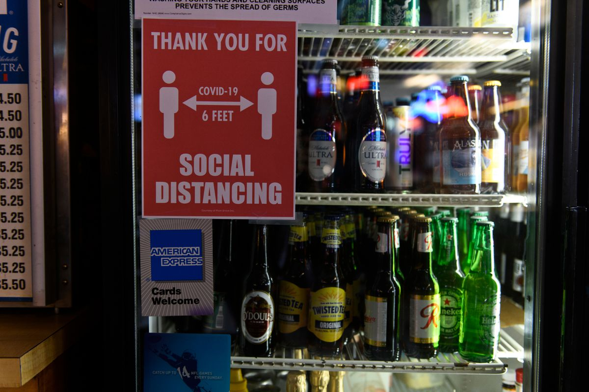 A social distancing sign is posted on a Crossroads Lounge refrigerator in May 2020. Starting Monday, May 3, physical distancing at businesses in the Municipality of Anchorage will be optional instead of required. (Marc Lester / ADN archive)