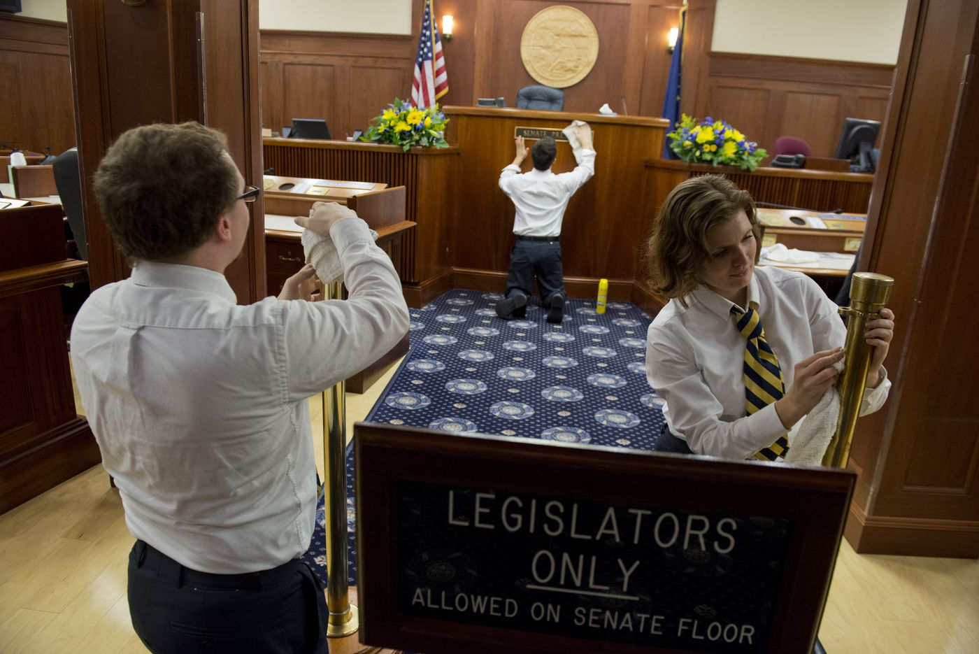 Senate pages, from left, Jacob Pennell, River Maketa and Sarah Bertram polish the wood and brass on the Senate floor in the Alaska state Capitol on the day before the legislative session begins.