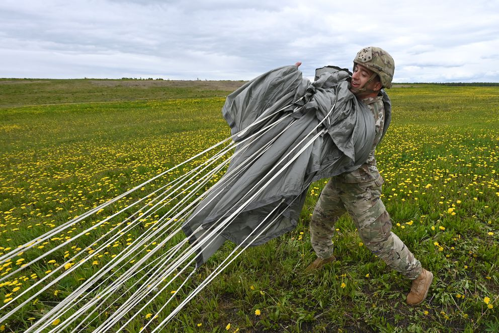 Sgt. William Alverson, with Breacher Company, 6th Brigade Engineer Battalion (Airborne) recovers his parachute after making his first-ever jump from a CH-47 Chinook helicopter on Tuesday. (Bill Roth / ADN)