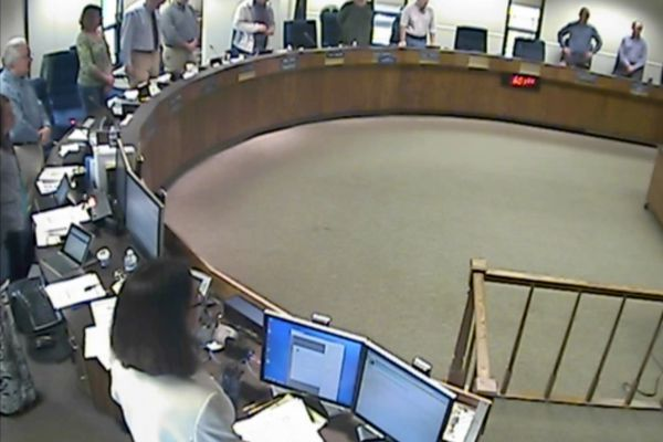 Members of the Kenai Borough Assembly stand during the invocation at the start of Tuesday's meeting. (Screengrab from Kenai Borough video)