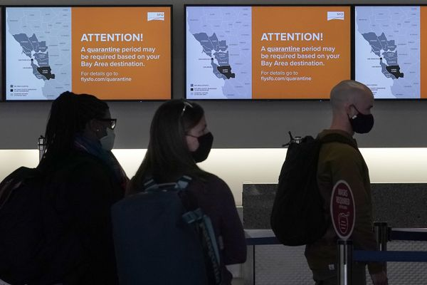 Signs advising possible quarantine requirements are shown as travellers wait in line at a Delta Air Lines gate at San Francisco International Airport during the coronavirus pandemic in San Francisco, Tuesday, Dec. 22, 2020. (AP Photo/Jeff Chiu)