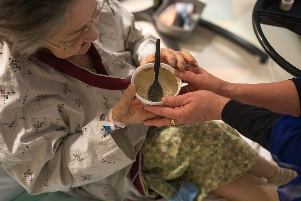 Food service manager Londa Shahan offers a cup of seal soup broth to Jean Hull, a patient at the Alaska Native Medical Center in Anchorage, on Jan. 22. The seal meat, one of a number of traditional Native foods offered each Tuesday, was donated by a subsistence hunter in Ketchikan.
