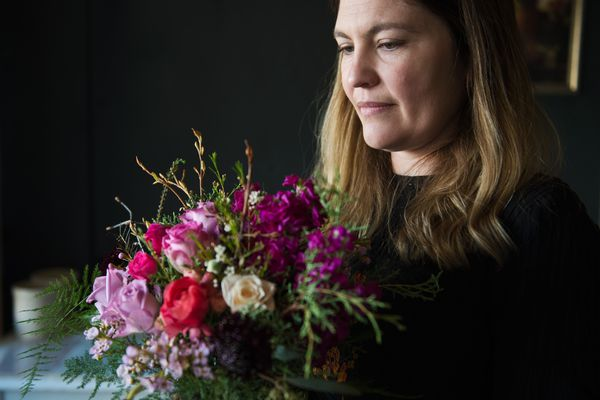 Dallas Wildeve holds an arrangement that includes birch branches, ranunculus, scabiossa and soapberry. Wildeve is the owner of Bloomsbury Blooms, located on 4th Avenue in downtown Anchorage. Photographed on March 21, 2018. (Marc Lester / ADN)
