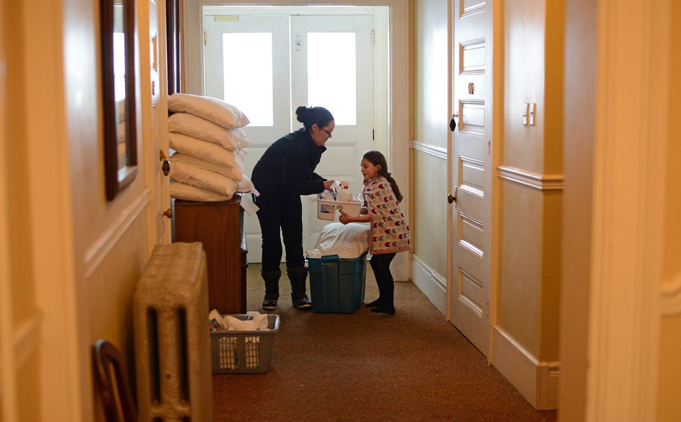 Geneva 'Gina ' Randles hands a container of cleaning supplies to her daughter, six-year-old Grace Comstock, as they prepare the Hotel Halsingland in Haines to accept guests. The hotel has been closed for a year and a half but is being reopened to accept relief workers. (James Brooks / ADN)