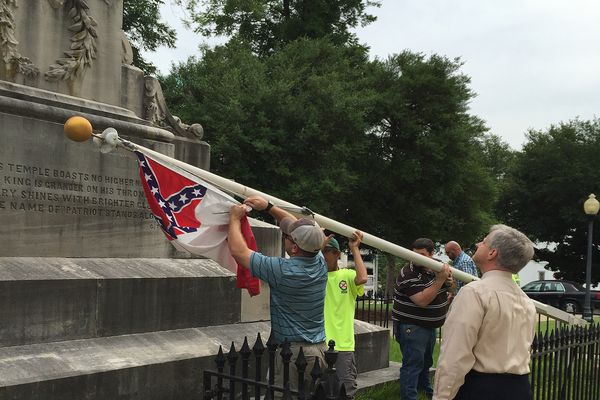 State workers take down a Confederate national flag on the grounds of the state Capitol, Wednesday, June 24, 2015, in Montgomery, Ala. Alabama Gov. Robert Bentley ordered Confederate flags taken down from a monument at the state Capitol.