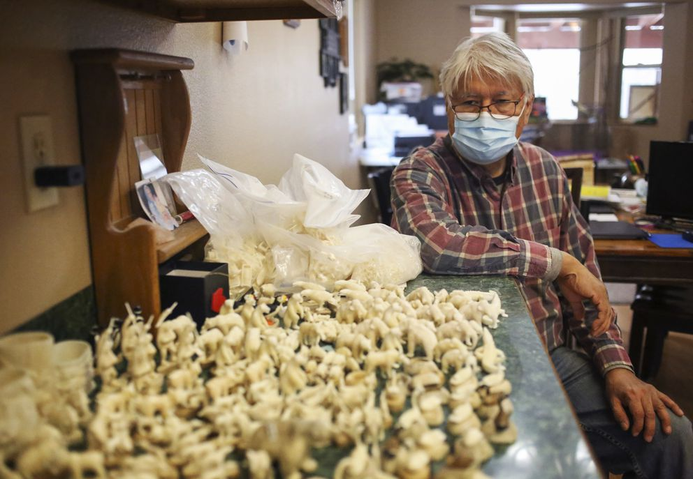 Leonard Savage sits next to hundreds of unsold ivory carvings he created at his home in Wasilla on Oct. 27, 2020. (Emily Mesner / ADN)