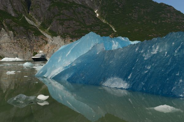 The charter yacht Rebel motors past a freshly calved iceberg in front of Sawyer Glacier.  (Bob Hallinen / ADN)