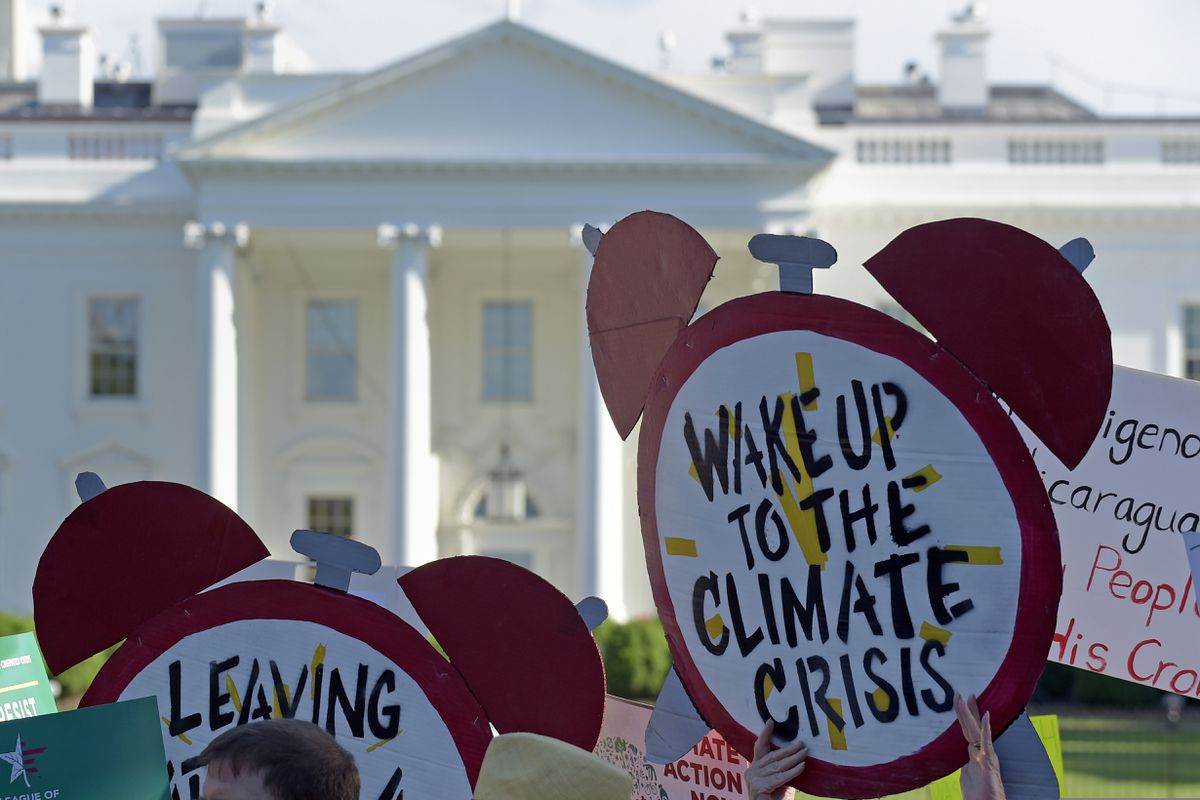 FILE- In this June 1, 2017 file photo, protesters gather outside the White House in Washington to protest President Donald Trump's decision to withdraw the Unites States from the Paris climate change accord. (AP Photo/Susan Walsh)