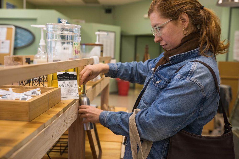 Helen Poitra-Chalmers fills a reusable container with bath and body oil on Thursday, Oct. 31, 2019 at Blue Market AK. The new retail business aims to minimize waste. (Loren Holmes / ADN)