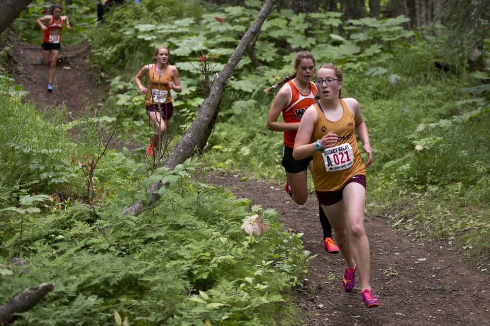 Dimond's Delainey Zock leads a line of runners through the Kincaid Park woods. (Marc Lester / ADN)
