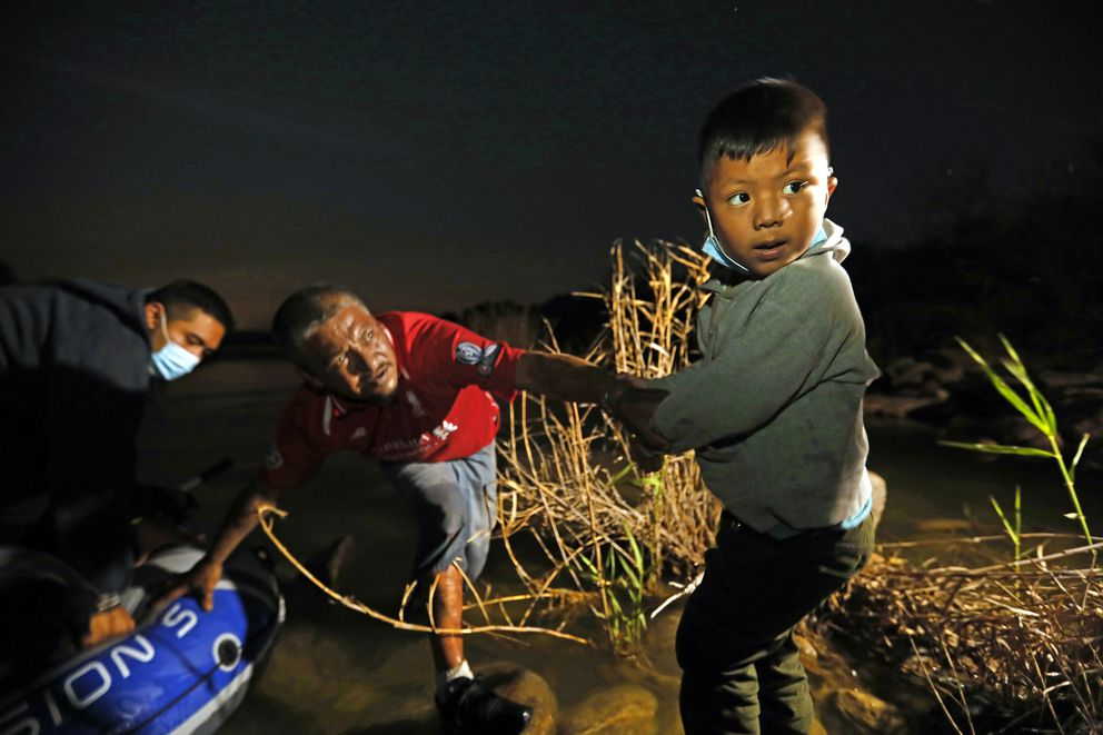 A young boy, Carlos, 5, from El Salvador gets help steadying himself on a rock as his father Eddy, 25, left, gets out of the raft after crossing the Rio Grande River on March 26, 2021 in Roma, Texas. (Carolyn Cole/Los Angeles Times/TNS)