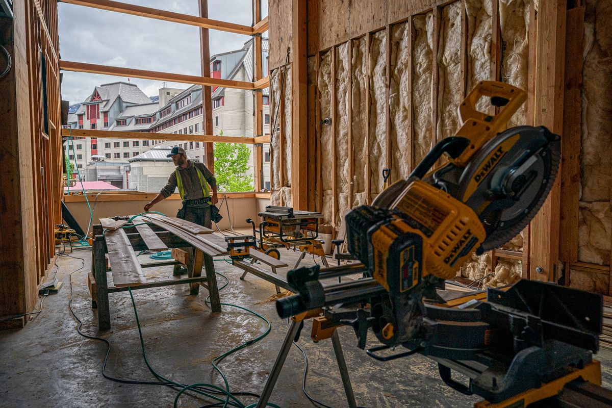 A construction worker cuts siding at the Alyeska Nordic Spa on Thursday, June 10, 2021 at Alyeska Resort in Girdwood. The new spa, adjacent to the existing Hotel Alyeska, is planned to open this fall. (Loren Holmes / ADN)