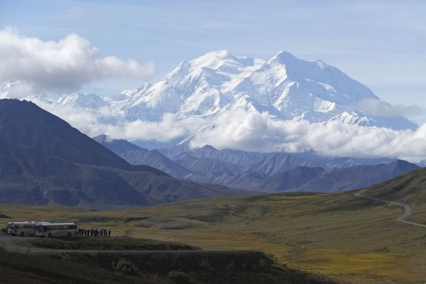FILE - In this Aug. 26, 2016, file photo sightseeing buses and tourists are seen at a pullout popular for taking in views of North America's tallest peak, Denali, in Denali National Park and Preserve, Alaska. The only road into Alaska's Denali National Park and Preserve has been closed in an effort to keep people home during the coronavirus pandemic, park officials announced Tuesday, April 14, 2020. Officials said in a release the closure of the 92-mile park road is in response to the Centers for Disease Control guidance and state of Alaska health mandates and travel restrictions to control the spread of the virus. (AP Photo/Becky Bohrer, File)