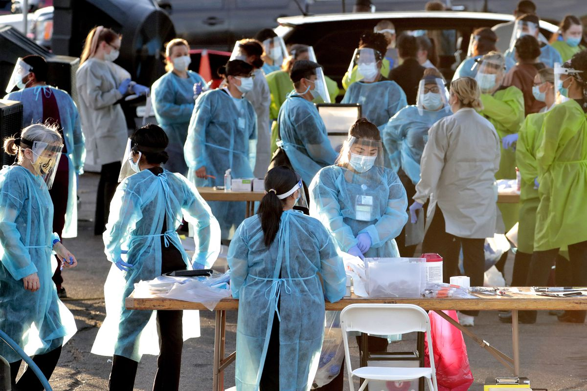 FILE - In this June 27, 2020, file photo, medical personnel prepare to test hundreds of people lined up in vehicles in Phoenix's western neighborhood of Maryvale for free COVID-19 tests organized by Equality Health Foundation. (AP Photo/Matt York, File)