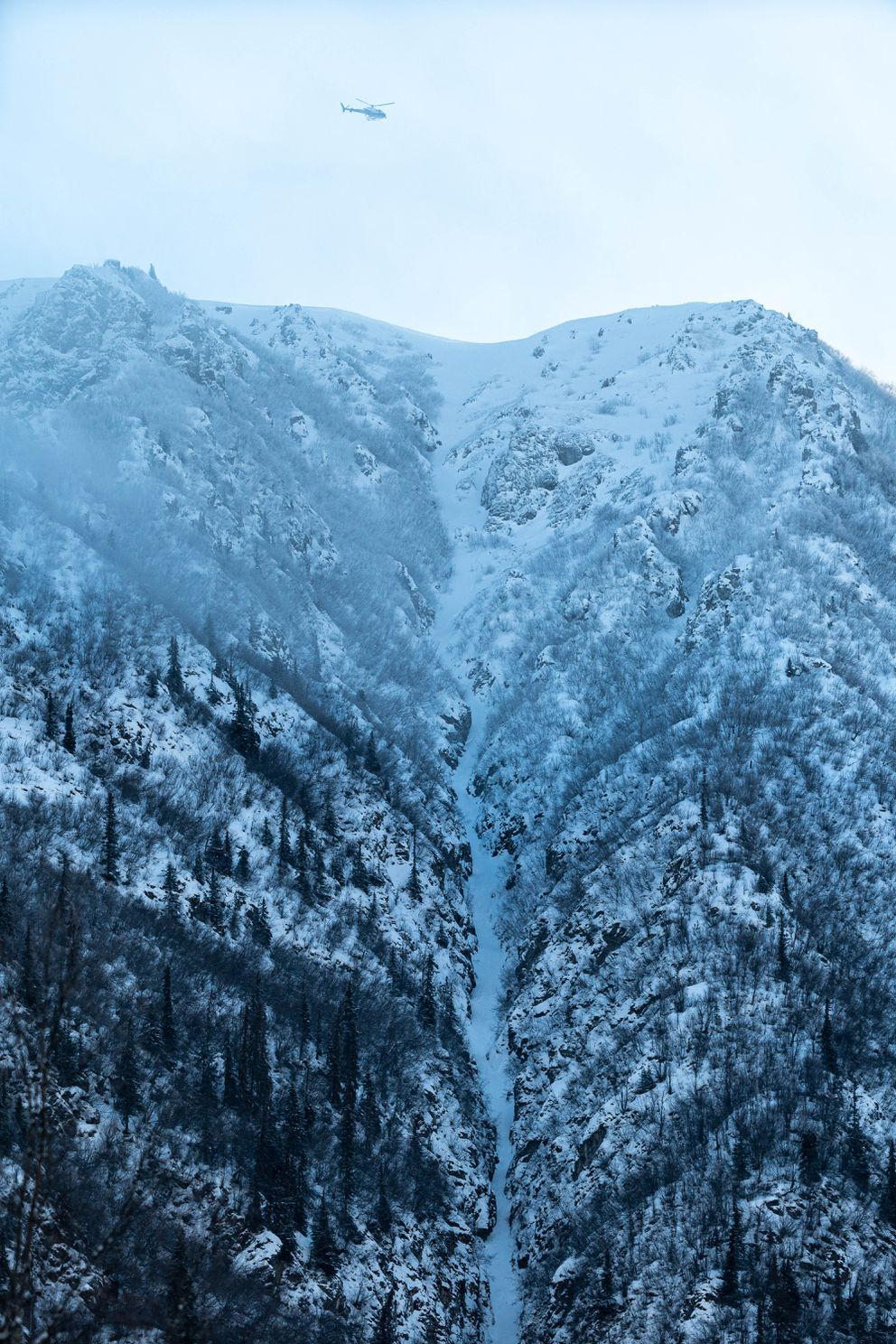 An Alaska State Troopers helicopter hovers over the Northwest Couloir of Bear Mountain on Thursday. (Loren Holmes / ADN)