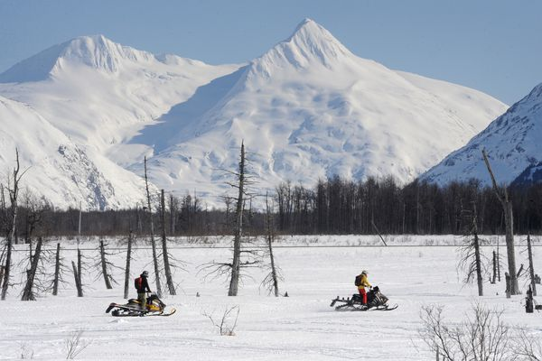 Snowmobilers ride across hard-packed snow near Portage in the sunshine on Monday, March 30, 2020. (Bill Roth / ADN)