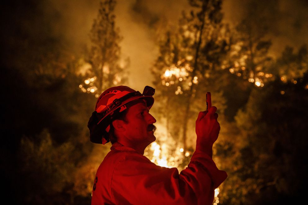 Firefighters monitor a burn operation and take a weather reading near Ladoga, Calif., on August 7, 2018. (Marcus Yam/Los Angeles Times/TNS)