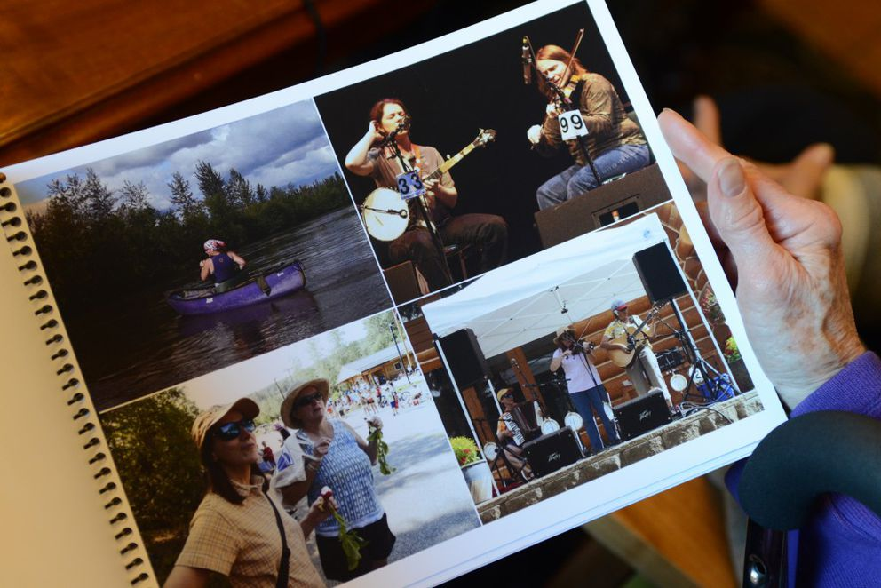 """Friends in her """"Glacial Erratics"""" Share the Care group review a photo album created for Sherri Hadley's celebration of life held two weeks earlier on Tuesday at The Marietta House assisted living home in Anchorage. (Erik Hill / Alaska Dispatch News)"""