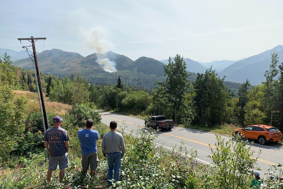 People gathered on Skyline Drive to watch a small wildfire burning on the south slope of the Meadow Creek Valley north of Eagle River on Monday, Aug. 12, 2019. (Matt Tunseth / Chugiak - Eagle River Star)