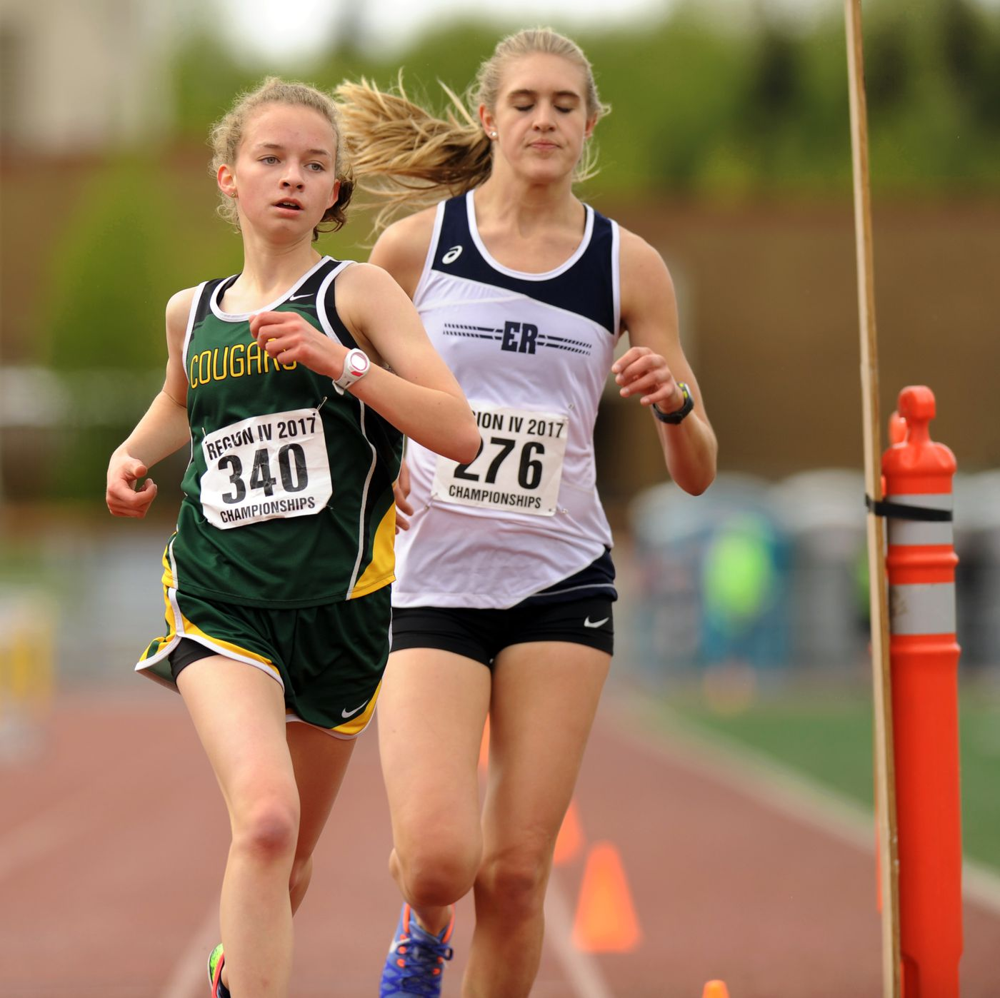 Grace Fahrney of Service, left, edges past Peyton Young of Eagle River with two laps to go before opening a gap to win the girls 3,200-meterrace. (Erik Hill / Alaska Dispatch News)