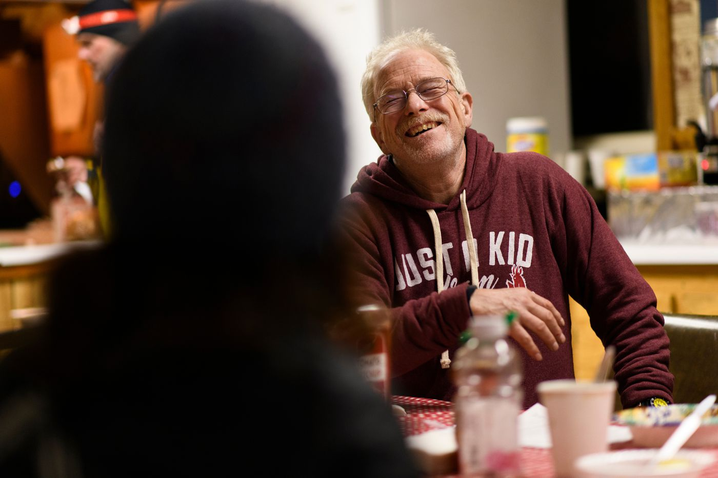 Jeff King laughs while talking with other mushers in the Takotna community hall on March 6. (Marc Lester / ADN)