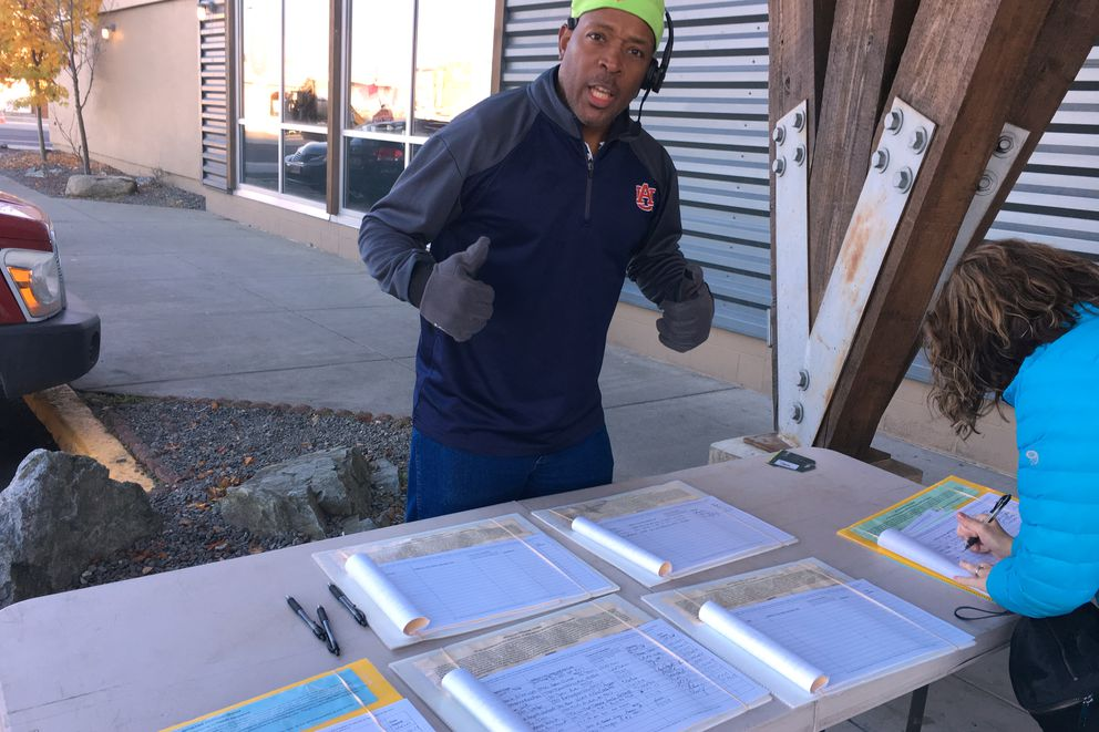 Arenza Thigpen Jr. collects petition signatures in support of citizens initiatives outside the Anchorage REI on Sunday, Oct. 15, 2017. (Nathaniel Herz / Alaska Dispatch News)