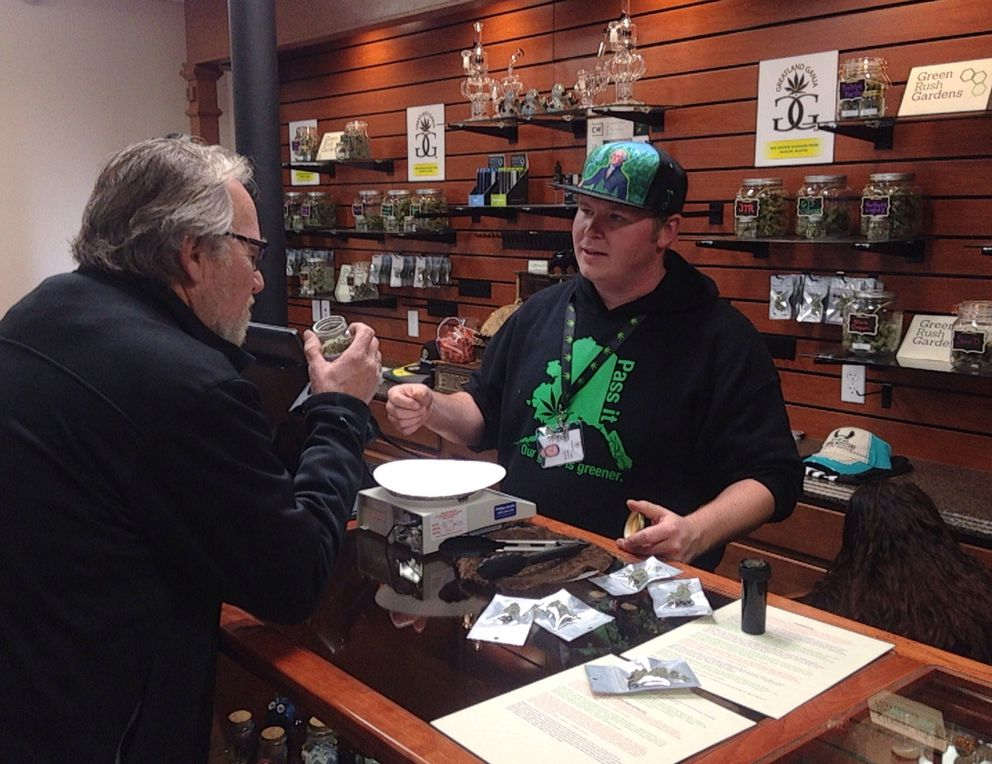 Valdez resident Michael Holcombe, left, was the first customer at Valdez store Herbal Outfitters during its grand opening as the first store in Alaska. Holcombe said he waited 46 years to buy legal marijuana. (Laurel Andrews / Alaska Dispatch News)