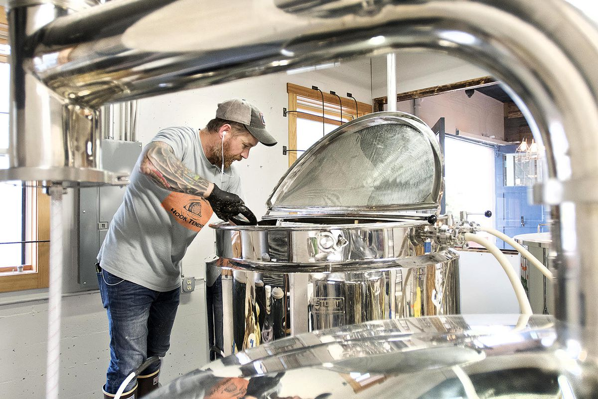 Owner Sean Heismann removes spent brewing mash from a brite tank at Bawden Street Brewing Co. in Ketchikanon July 23. Since the brewery's July 16 opening, its beer has been in high demand, and the business is already providing beer to four local bars. (Dustin Safranek / Ketchikan Daily News)