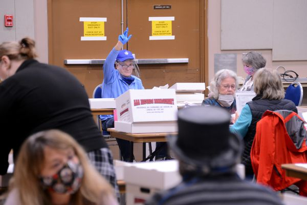 Jim Carroll raises his hand for attention during the randomized hand-count double-check following Alaska's Aug. 18, 2020 statewide primary election. Carroll was among the teams of workers who gathered in Juneau, Alaska's Centennial Hall to hand-count ballots from across the state. (James Brooks / ADN)
