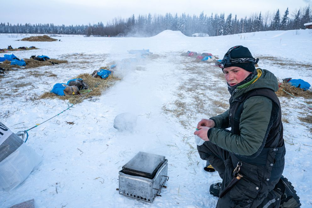 Fabio Berlusconi heats water for his team in Nikolai on Wednesday, March 11, 2020 during the Iditarod Trail Sled Dog Race. (Loren Holmes / ADN)