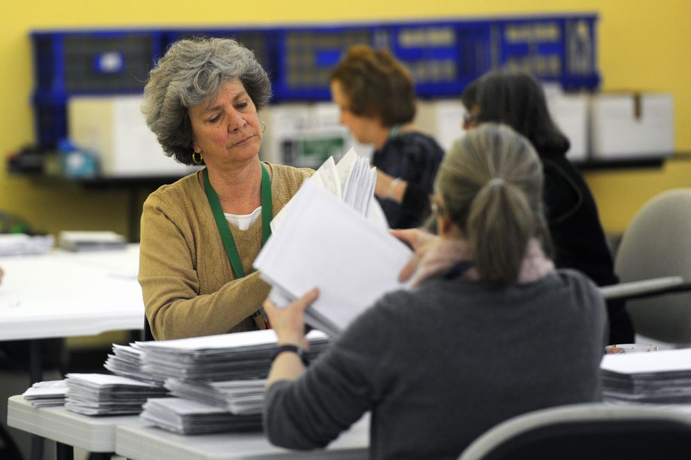 Lo Hansen, left, and Cindy Hawkins prepare absentee and early voting ballots from the Loussac Library polling station for counting on Tuesday as the review team works at the new municipal election center at Ship Creek on Monday. (Erik Hill / Alaska Dispatch News)