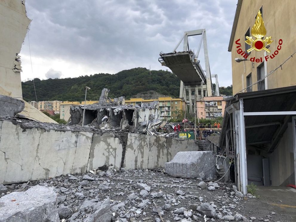 In this photo released by the Italian firefighters, rescue teams work among the rubble of the collapsed Morandi highway bridge in Genoa, northern Italy, Tuesday, Aug. 14, 2018. A bridge on a main highway linking Italy with France collapsed in the Italian port city of Genoa during a sudden, violent storm, sending vehicles plunging 90 meters (nearly 300 feet) into a heap of rubble below. (Vigili Del Fuoco via AP)