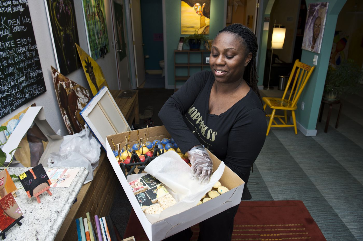 LaTasha McKnight carries a box of cake pops and other desserts she prepared for an art opening.  (Marc Lester / ADN)