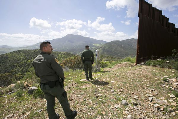 From left, Border Patrol Agents Fabian Carbajal and Justin Castrejon stand at the end of a section of border fence just east of Marron Valley in southeast San Diego County. (John Gibbins/San Diego Union-Tribune/TNS)