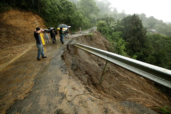 Residents look at a road partially collapsed following heavy rains of Tropical Storm Nate that affects the country in El Llano de Alajuelita, Costa Rica, October 5, 2017. REUTERS/Juan Carlos Ulate