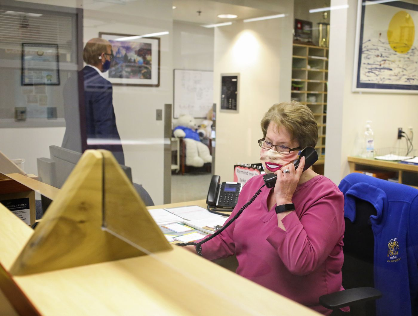 Main Office Secretary Elise VonHoldt answers a phone call from a parent on the first day of school at Bartlett High School. (Emily Mesner / ADN)