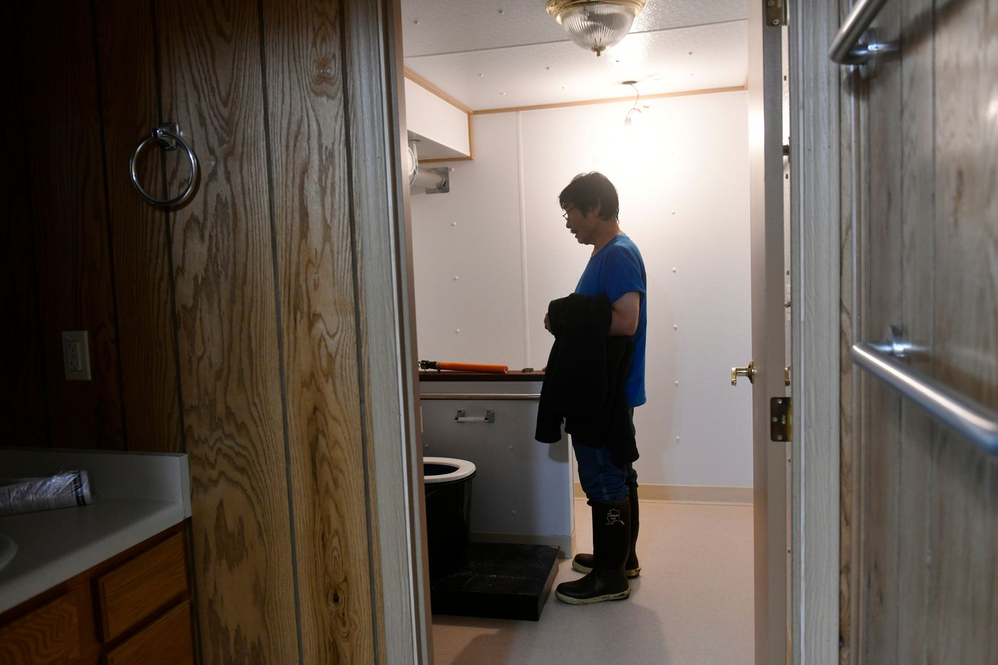 Paul Charles, member of the Newtok Village Council, looks at the portable alternative sanitation system, or PASS, in his new Mertarvik home. The system is designed, in part, to catch rainwater and minimize exposer to pathogens. (Marc Lester / ADN)