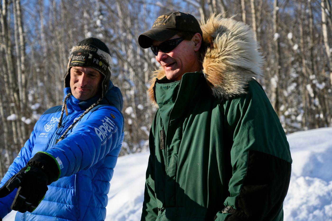 Iditarod chief veterinarian Stuart Nelson, right, talks with people at Iditarod Headquarters in Wasilla on March 4, 2020. (Marc Lester / ADN)