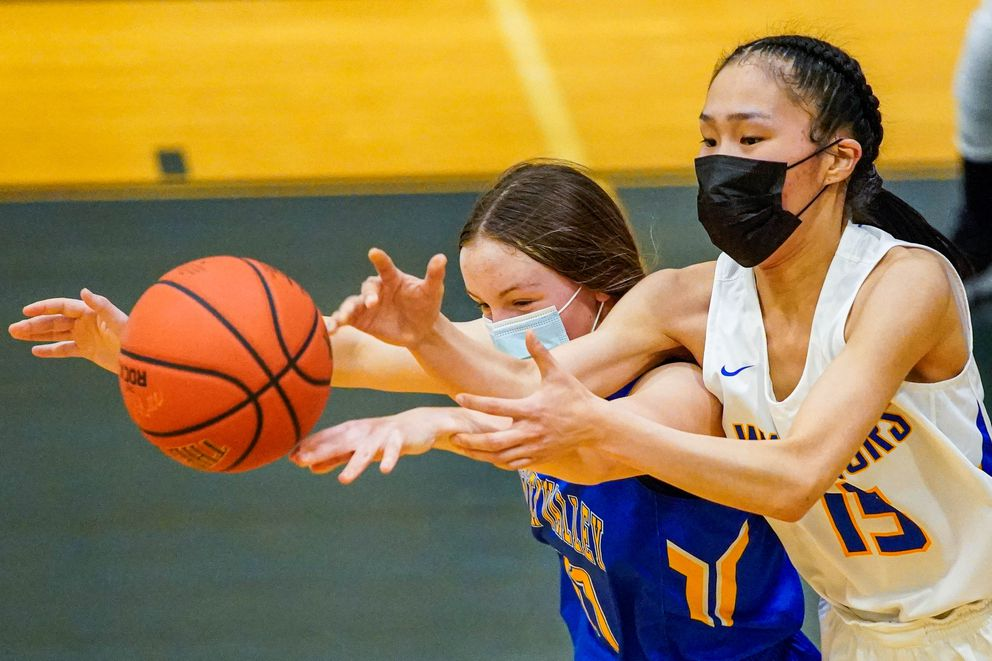 Su Valley's Bethany Kehoe and Hooper Bay's Mary Long reach for the ball during the game. (Loren Holmes / ADN)