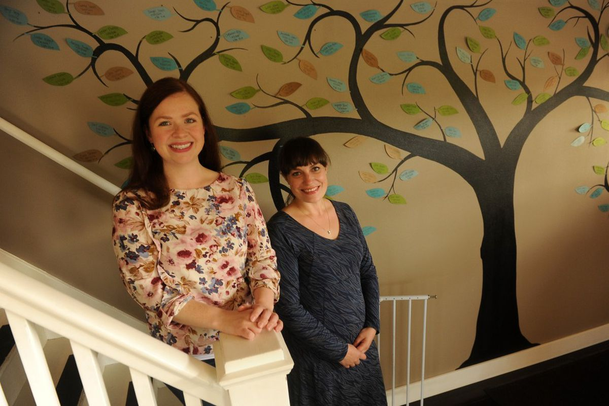 Stormy Antonovich, staff midwife, and Lena McGinnis-Kilic, midwife and owner of Heritage Birth Center, pose for a photograph in front of a tree with the names of babies born there on its leaves, at the Ninth Avenue facility on Friday, August 5, 2016 in Anchorage, AK. (Bob Hallinen / Alaska Dispatch News)