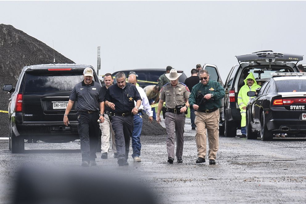 Law enforcement officers gather near the scene where the body of a woman was found near Interstate 35 north of Laredo, Texas on Saturday, Sept. 15, 2018. A U.S. Border Patrol agent suspected of killing four women was arrested early Saturday after a fifth woman who had been abducted managed to escape from him and notify authorities, law enforcement officials said, describing the agent as a 'serial killer. ' (Danny Zaragoza/The Laredo Morning Times via AP)