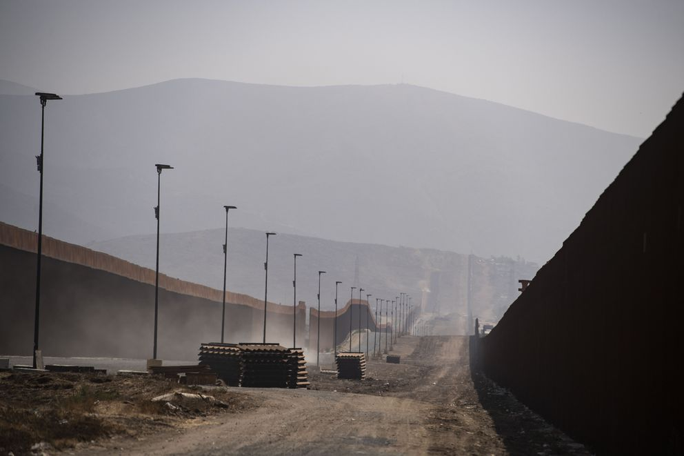 Sections of fencing rest between the border barriers that separate the United States and Mexico in the San Diego area. (Washington Post photo by Carolyn Van Houten)